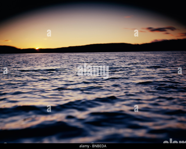 Select focus image of sun behind some trees on a lake - Stock Image