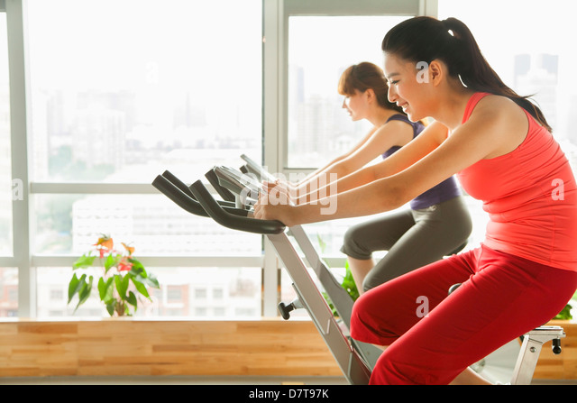 Young women on stationary bikes exercising in the gym - Stock Image