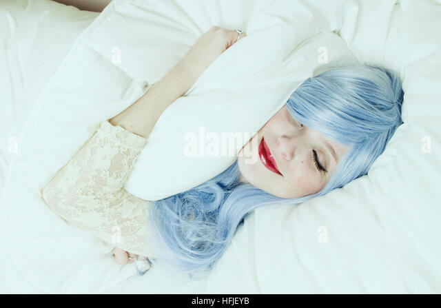 Young woman smiling while sleeping in her bed hugging her pillow - Stock Image