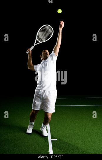 A tennis player serving a ball, portrait, studio shot - Stock Image