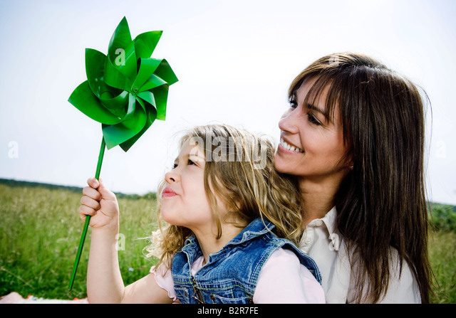 Woman and girl with toy windmill - Stock Image