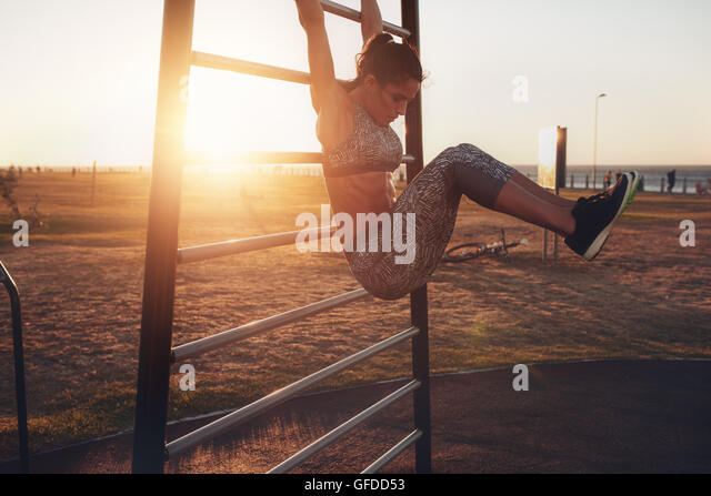 Candid shot of real healthy and fit woman performing hanging leg raises on outdoor fitness station in sunset at - Stock Image