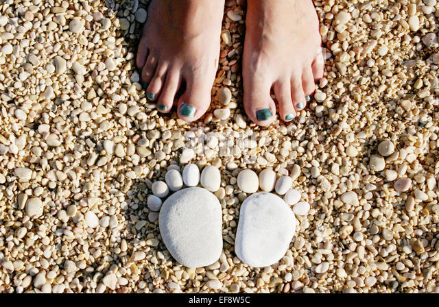 Croatia, Stones in shape of feet in front of woman's feet - Stock Image