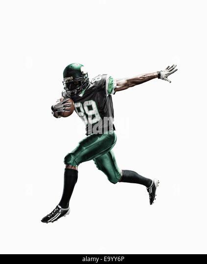 Studio shot of male football player running with ball - Stock-Bilder