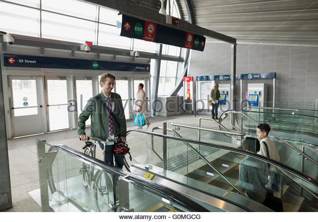 Businessman with bicycle at escalator in train station - Stock Image