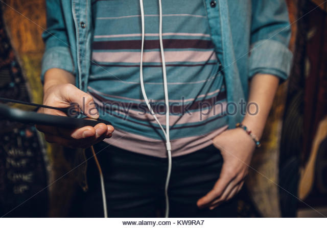 Close up midsection tween girl with headphones texting with smart phone - Stock Image
