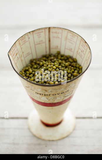 Uncooked green mung beans in a vintage measuring cup on a rustic wood surface. - Stock Image