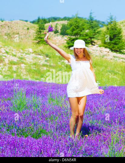 Cute girl wearing white hat holding in hand beautiful purple lavender flowers, dancing on floral glade, summer time - Stock Image