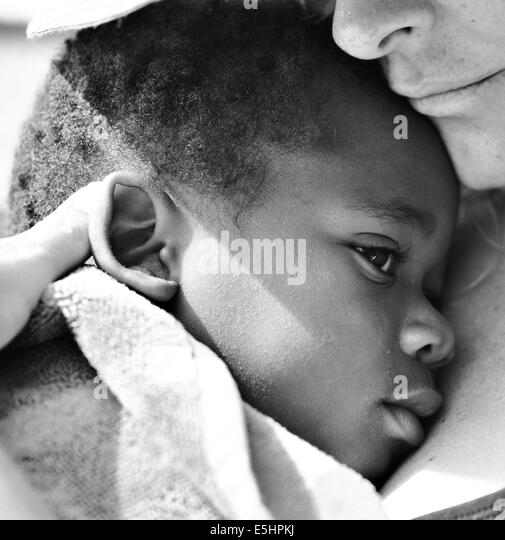 Toddler/baby in BW laying with mom wrapped in a towel - Stock Image