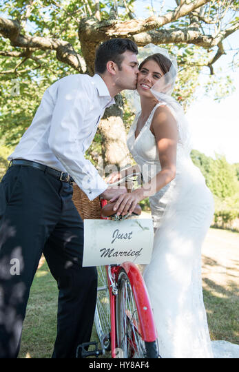 A bride and groom with a bicycle on their wedding day - Stock Image