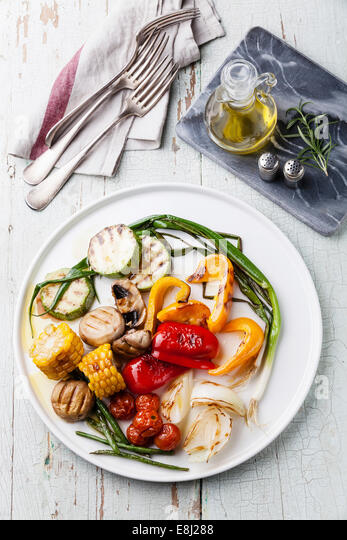Grilled vegetables on the white plate on blue textured background - Stock Image