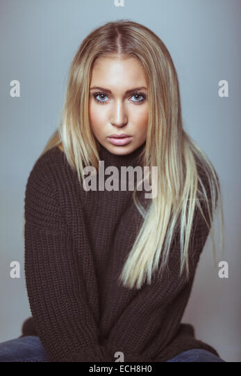 Portrait of beautiful young blond woman in sweater looking at camera. Caucasian female model against white wall. - Stock Image