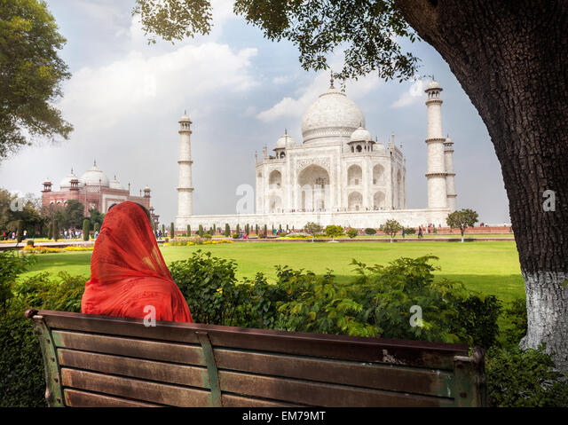 Woman in red scarf sitting on the bench in the shadow and looking at Taj Mahal in Agra, Uttar Pradesh, India - Stock-Bilder