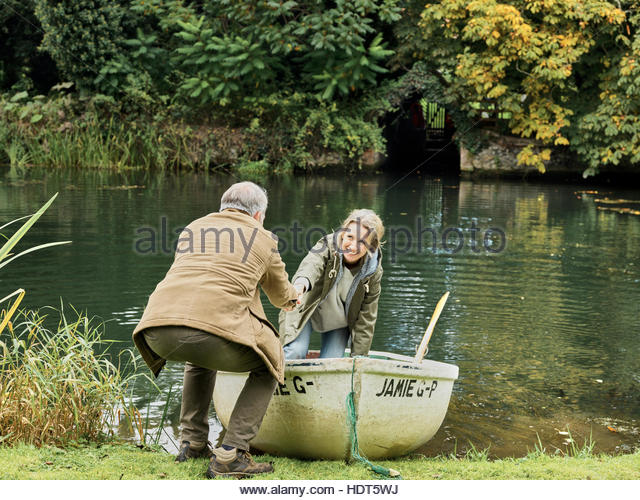 Mature man helping his wife out of row boat. - Stock Image