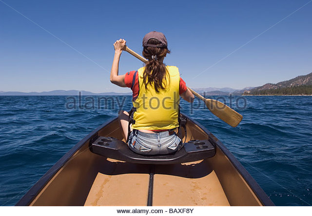 Rear view of woman paddling canoe - Stock Image