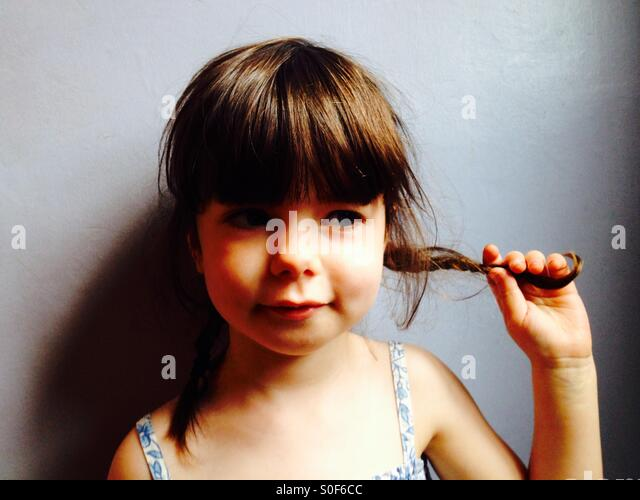 3-year old girl holding her pigtails - Stock Image