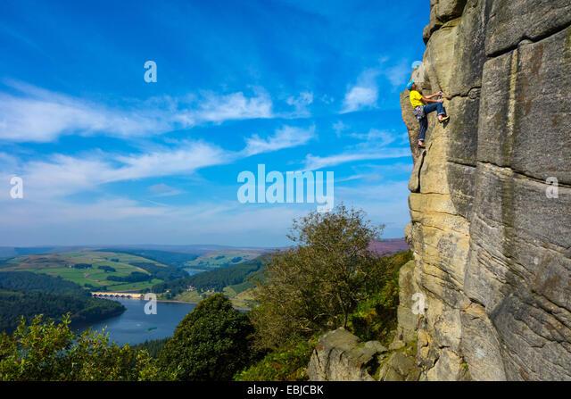 Rock climber on Bamford Edge, Derbyshire, Peak District, with Ladybower Reservoir - Stock Image