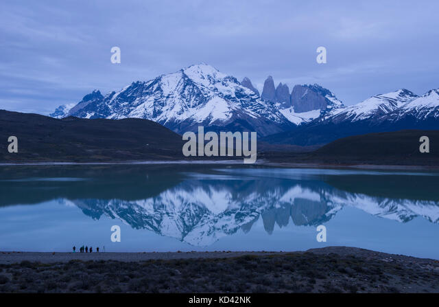 Torres del Paine mountains reflecting on the surface of Laguna Amarga, with tourists taking photos in the foreground - Stock Image