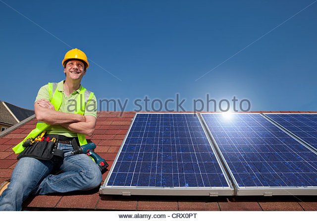 Portrait of smiling engineer sitting on rooftop next to solar panels with arms crossed - Stock Image