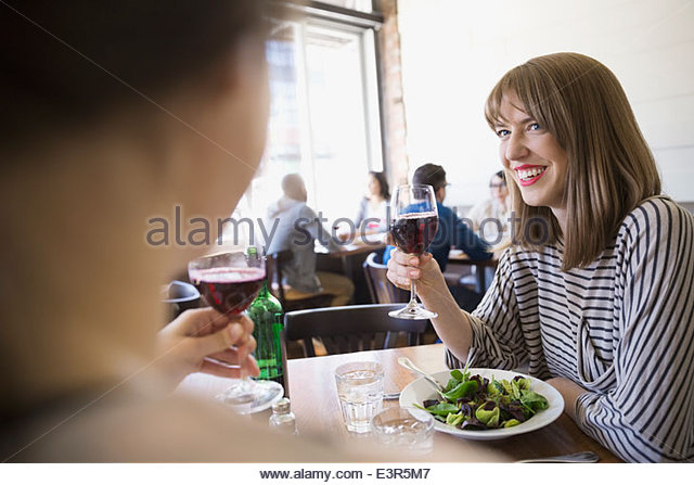 Women enjoying lunch and wine at bistro - Stock Image