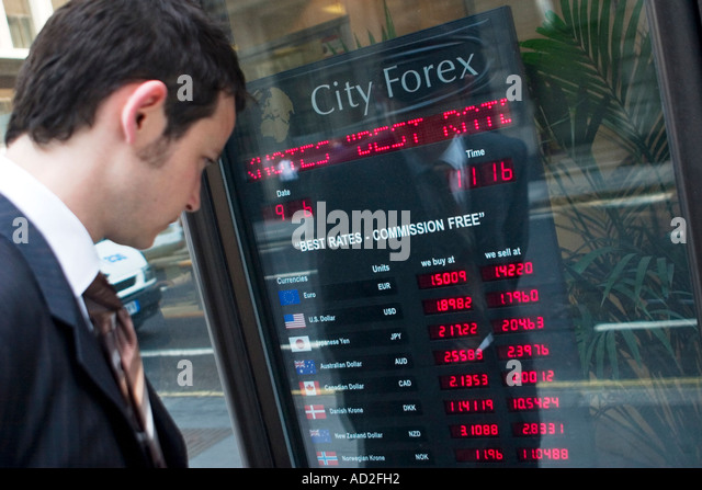 Young businessman looks at foreign exchange rates board in the City of London - Stock Image