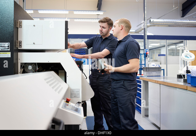 Workers checking control panel in engineering factory - Stock Image