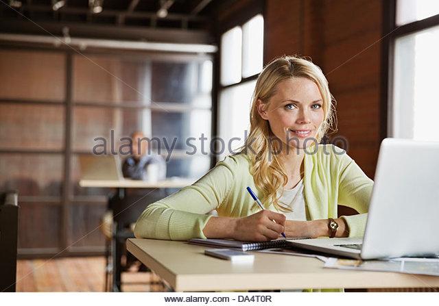Portrait of female entrepreneur sitting at desk in office - Stock-Bilder