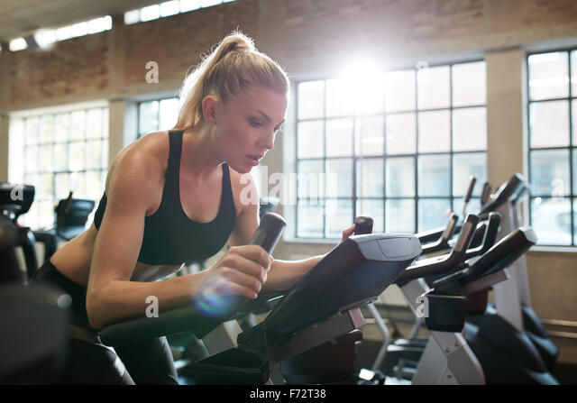 Fit woman working out on exercise bike at the gym. Indoor shot of a female doing fitness training on spinning bicycle - Stock Image