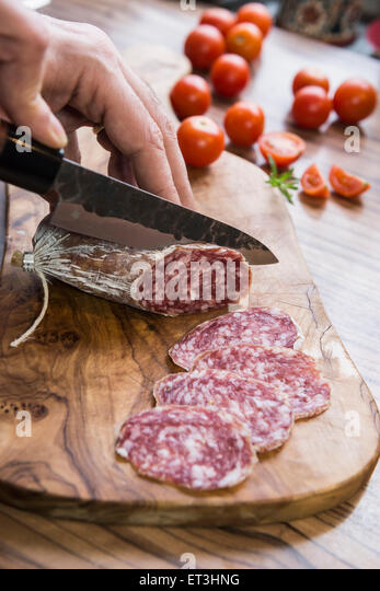 Person's hand chopping sausage with knife, Germany - Stock Image
