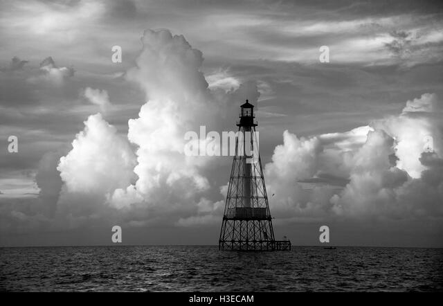 Once the site of a shipwreck, Alligator Reef Light looks beautiful at dawn with summer clouds side-lit by the rising - Stock Image