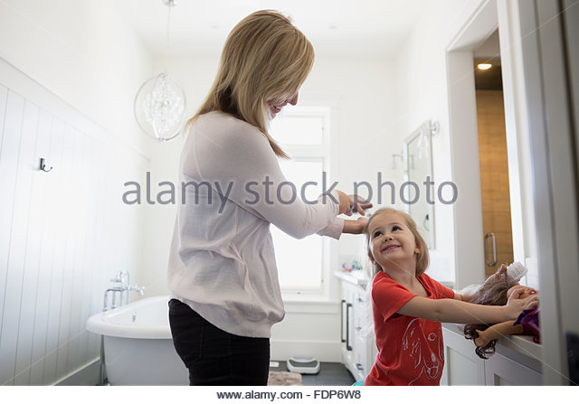 mother brushing daughters hair bathroom - Stock Image