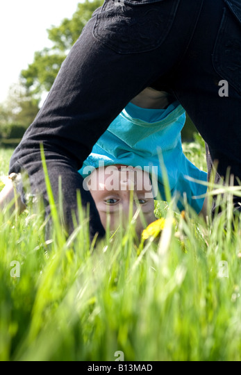 young boy doing handstand in summer field - Stock-Bilder