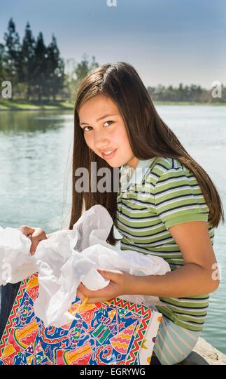 Teenage Vietnamese/Caucasian girl opening  presents gifts outside smiling at camera. MR  © Myrleen Pearson. - Stock-Bilder
