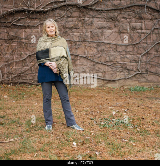 Senior woman standing against wall covered in leafless ivy - Stock Image
