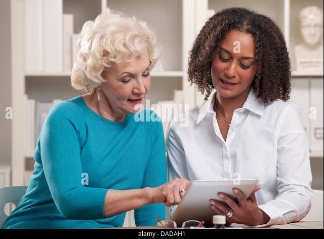 Two women using digital tablet - Stock-Bilder
