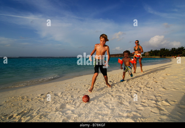 Children playing football on the beach of Laguna Resort, The Maldives, Indian Ocean - Stock-Bilder