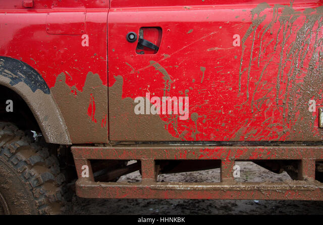 Mud splashes on the side of a bright red Land Rover - Stock Image