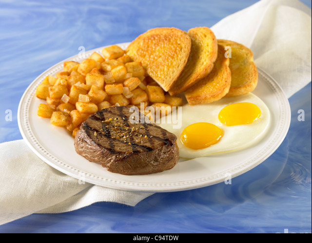 A steak breakfast with two eggs, potato and toast - Stock Image