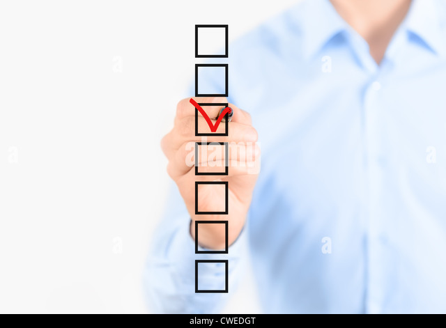 Young businessman checking mark on checklist with marker. Isolated on white. - Stock Image