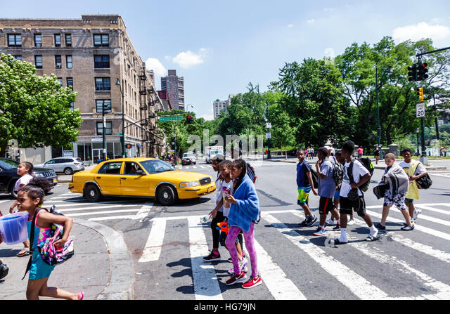 Manhattan New York City NYC NY Spanish Harlem street crossing traffic intersection Black boy girl teen student walking - Stock Image