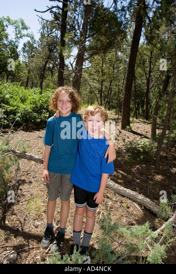 Two boys standing together in a forest - Stock-Bilder