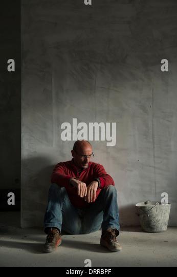 Depressed man sitting on the floor - Stock Image