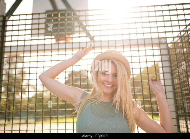 Portrait of young female basketball player holding onto wire fence - Stock Image