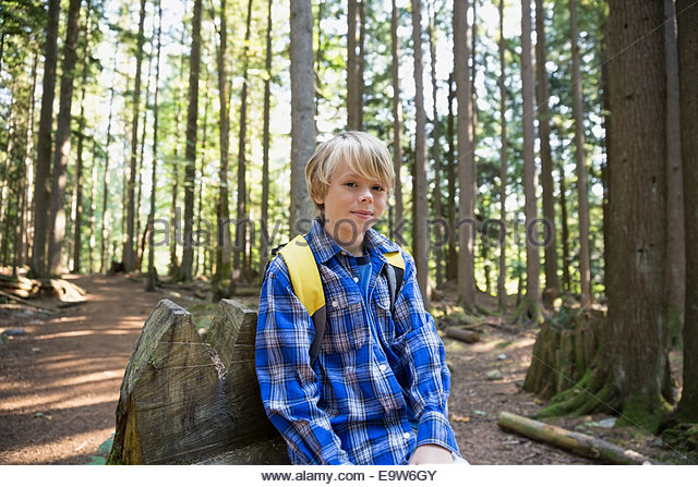 Portrait of boy with backpack in woods - Stock Image