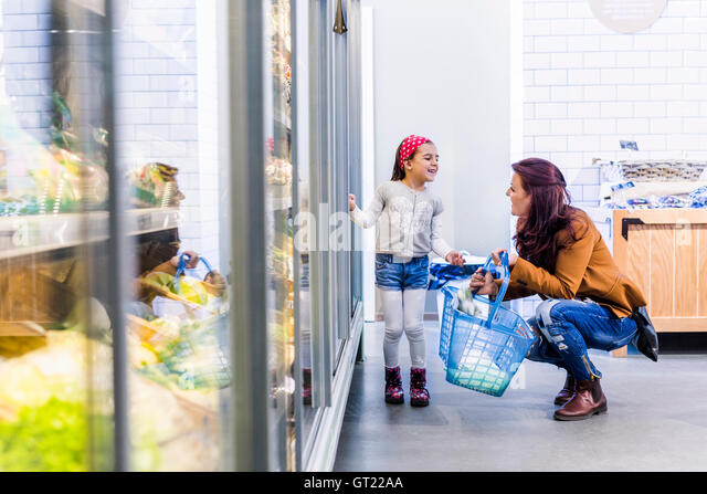 Happy mother and daughter at refrigerated section in supermarket - Stock-Bilder