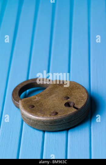 Old fashioned padlock on a blue wooden background - Stock-Bilder