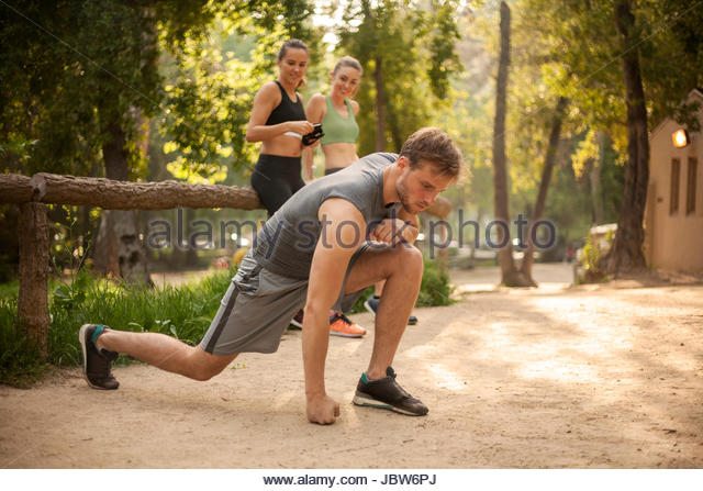 Young man exercising outdoors, two young women leaning against fence, watching man - Stock-Bilder