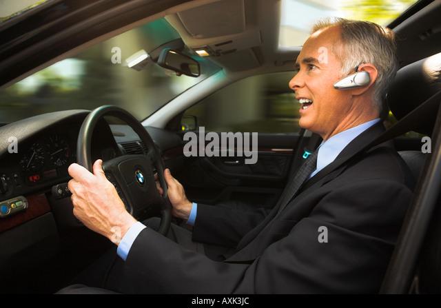 business work job career old elderly man sitting driving steering fast happy in new car holding wheel sunroof talking - Stock Image