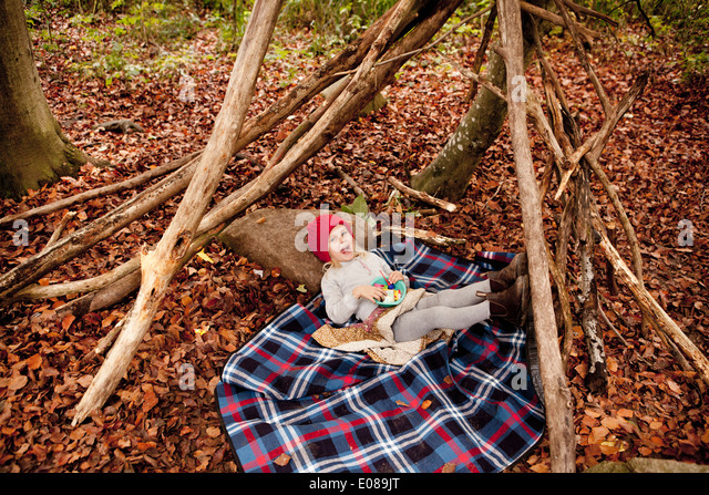 Full length portrait of girl lying on picnic blanket in forest - Stock Image