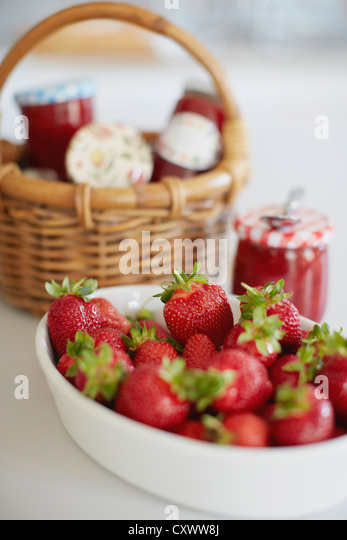 Bowl of strawberries with jars of jelly - Stock Image